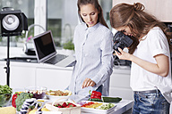 Woman photographing food in kitchen - ABIF00039