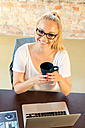 Portrait of smiling businesswoman sitting with coffee mug at desk - SPCF00248