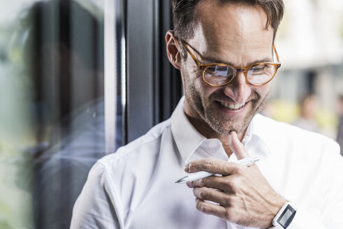 Portrait of laughing businessman wearing glasses and smartwatch - UUF12063