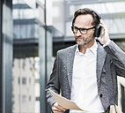 Portrait of businessman with documents and headphones - UUF12081