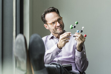 Portrait of smiling man with atomic model - UUF12087