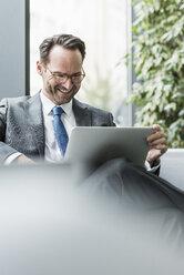 Businessman sitting in lobby using laptop - UUF12096