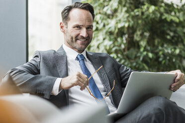 Portrait of smiling businessman sitting in lobby with laptop - UUF12099