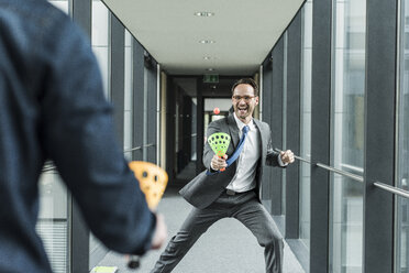 Businessman playing with colleague on the corridor - UUF12102