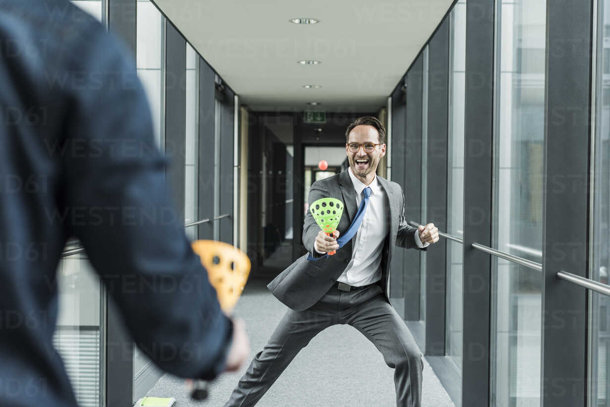 Businessman playing with colleague on the corridor - UUF12102 - Uwe Umstätter/Westend61