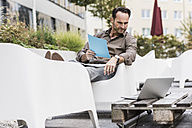 Man with documents sitting on terrace looking at laptop - UUF12108