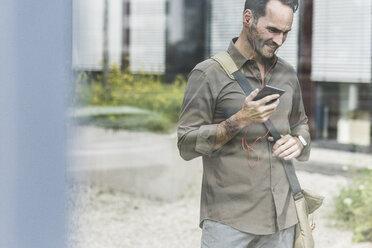 Portrait of smiling businessman using smartphone and earphones - UUF12114