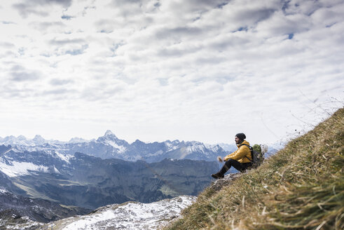 Germany, Bavaria, Oberstdorf, hiker sitting in alpine scenery - UUF12139