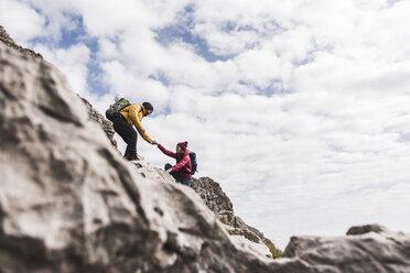 Germany, Bavaria, Oberstdorf, man helping woman climbing up rock - UUF12145