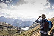 Germany, Bavaria, Oberstdorf, hiker with binoculars in alpine scenery - UUF12175