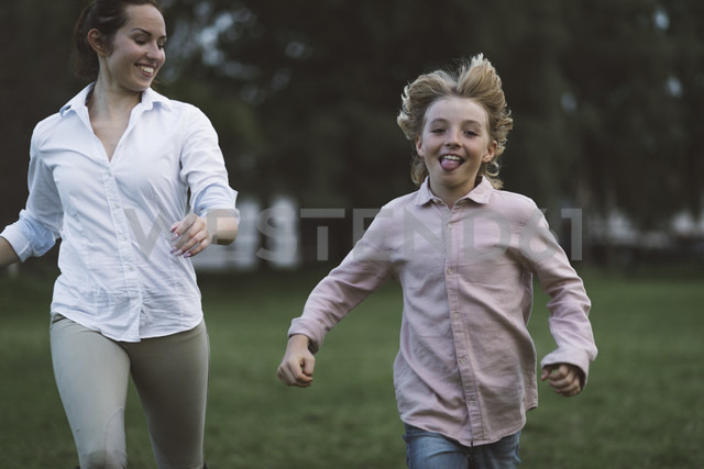 Boy and young woman running on a paddock - KMKF00042
