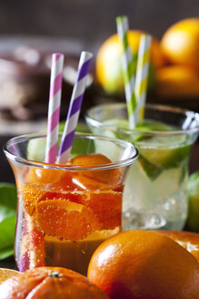 Fruit spritzer of tangerines and lime in a glass with drinking straws - CSF28483