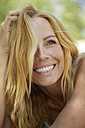 Portrait of happy strawberry blonde woman with freckles - PNEF00224