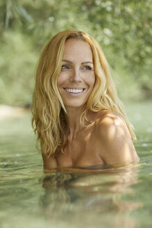Portrait of laughing blond woman bathing in lake - PNEF00227