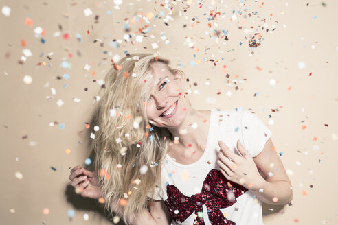 Laughing young woman with flying confetti - PNEF00233