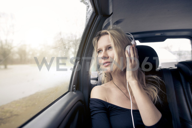 Portrait of young woman sitting in car listening music with headphones - PNEF00236