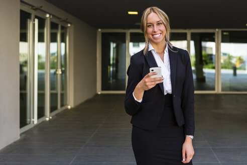 Portrait of laughing businesswoman with cell phone - MGIF00180