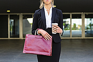 Businesswoman with fashionable red leatherbag and coffee to go, partial view - MGIF00183