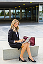 Businesswoman with fashionable leatherbag and coffee to go sitting on bench using laptop - MGIF00186