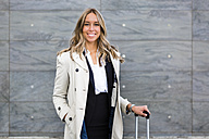 Portrait of smiling businesswoman with suitcase wearing trench coat - MGIF00192