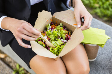 Businesswoman having lunch outdoors, partial view - MGIF00201