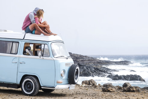 Spain, Tenerife, young couple in love relaxing on car roof of van - SIPF01830