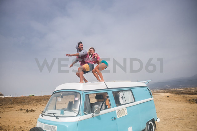 Spain, Tenerife, laughing young couple standing on car roof enjoying freedom - SIPF01833