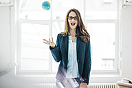 Portrait of businesswoman throwing small globe in the air - MOEF00179
