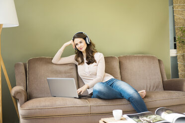 Young woman with headphones sitting on couch using laptop - MOEF00188
