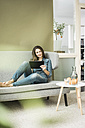 Young woman sitting on the couch using tablet - MOEF00194