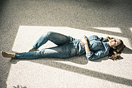 Young woman lying on carpet in the living room enjoying sunlight - MOEF00197