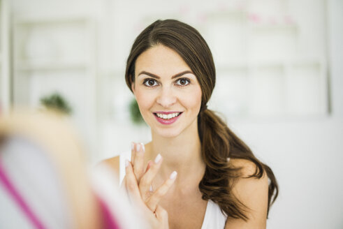Portrait of woman creaming her hands - MOEF00200