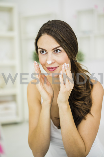 Portrait of smiling young woman creaming her face - MOEF00203