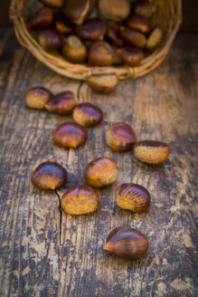 Roasted sweet chestnuts in a basket and on wood - LVF06360