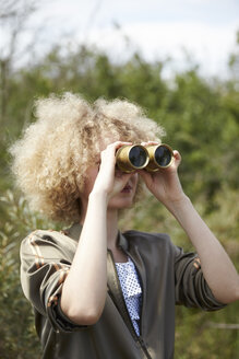 Young woman with curly hair looking through old binoculars - TSFF00140