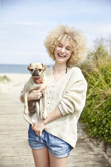 Portrait of laughing young woman holding dog on her arms - TSFF00146