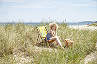 Young woman sitting on beach chair in the dunes watching something - TSFF00149