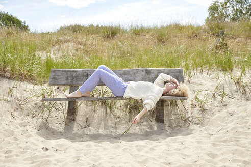 Young woman relaxing on bench in beach dunes - TSFF00155