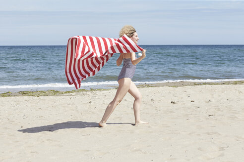 Smiling young woman with beach towel in front of the sea - TSFF00161