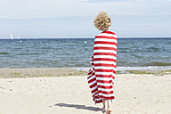 Back view of young woman wrapped in beach towel standing in front of the sea - TSFF00164