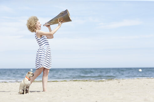 Young woman with megaphone and dog on the beach - TSFF00167