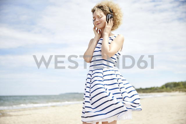 Portrait of young blond woman with headphones on the beach - TSFF00170 - Rosa Hellregen/Westend61