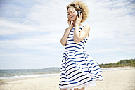 Portrait of young blond woman with headphones on the beach - TSFF00170