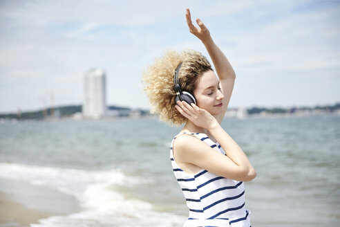 Portrait of young blond woman with headphones on the beach - TSFF00173