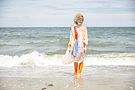 Smiling young woman wearing rain coat and Wellington boots standing at seaside - TSFF00179
