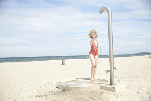 Young woman blond woman taking shower on the beach - TSFF00182