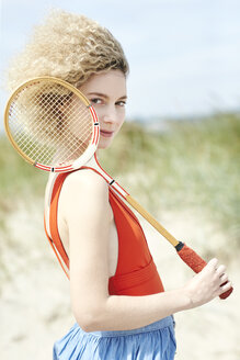 Portrait of young woman with tennis racket on the beach - TSFF00185