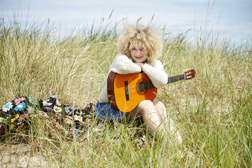 Portrait of young woman with guitar relaxing in beach dunes - TSFF00188