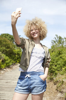 Portrait of smiling young blond woman taking selfie with smartphone - TSFF00194