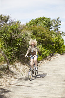 Happy young woman riding bicycle - TSFF00197